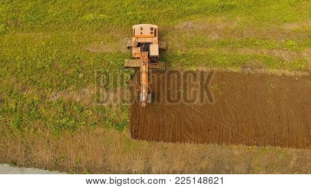 Excavator is digging an irrigation canal. Aerial view:Excavator digging a deep trench.excavator is digging an drainage canal in the agricultural field.