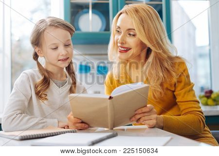 Funny reading. Pretty inspired blond slim mother smiling and looking at her daughter and while sitting at the table and her daughter reading
