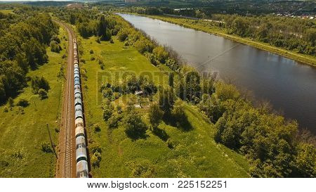 Freight train with cisterns and containers on the railway. Railway and highway with cars. Aerial view Container Freight Train, Locomotive in the countryside.