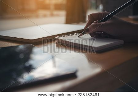 Closeup image of woman's hand writing on a blank notebook with laptop and tablet on wooden table background