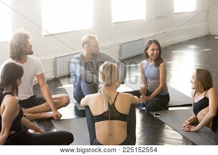 Group of young sporty people talking in a circle. Enjoy conversations with coacher and trainer, thinking of training practice successes and failures, having recovery and rest time after or before practice