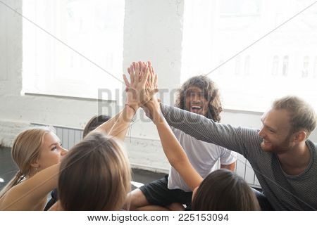 Group of young sporty people giving a high five, slapping the palms with hands raised above, well done concept, team training for spirit, fun, and motivation, victory or celebration gesture