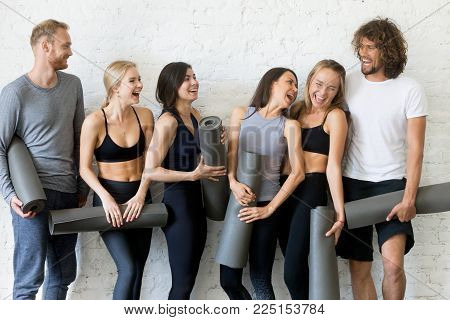 Group of laughing young sporty people standing at white wall. Having rest after practices, inviting, social atmosphere in yoga club, portrait of smiling students spending good time, indoor loft studio