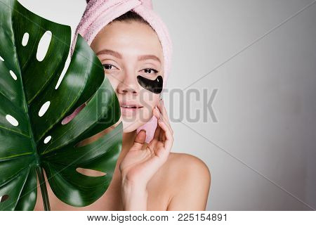 a woman with a towel on her head after showering patches under her eyes and holding a green leaf in her hand