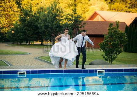 Young couple jumping in the swimming pool in a wedding suit and wedding dress. Sunny day.