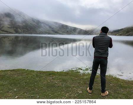 man with long sleeve t-shirt takes photographs of mountain at lakeside in New Zealand