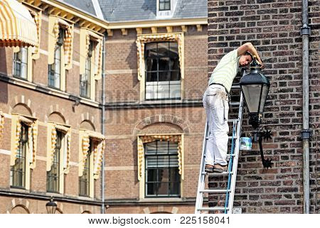 THE HAGUE, NETHERLANDS - APRIL 2: Working handyman on the ladder in front of building of dutch parliament at the city The Hague April 2, 2014 in The Hague