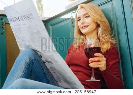 Staying informed. Beautiful relaxed fair-haired young woman smiling and reading a newspaper and holding g a glass of good red wine