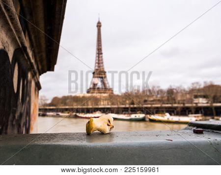 Bitten apple core left on Paris bridge with eiffel Tower in the background