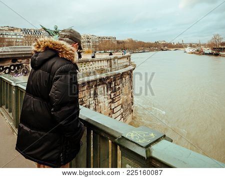 PARIS, FRANCE - JAN 30, 2018: Parisian senior man watch the swollen river Seine near the Eiffel Tower as the river's embankments overflow after days of heavy rain