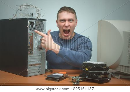 Computer repairman swears on users and shows a computer power button means turn off and turn on. Computer technician. PC repair service center.