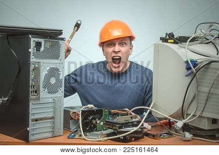 Enraged computer technician man is screaming and breaks a PC by hammer. PC repair service center. Mad system administrator in stress overburdened by work.