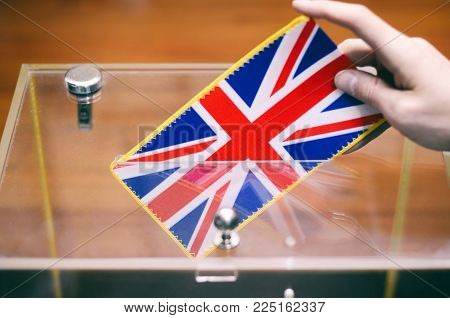 Man inserting United Kingdom flag into ballot box, voting and elections in United Kingdom.