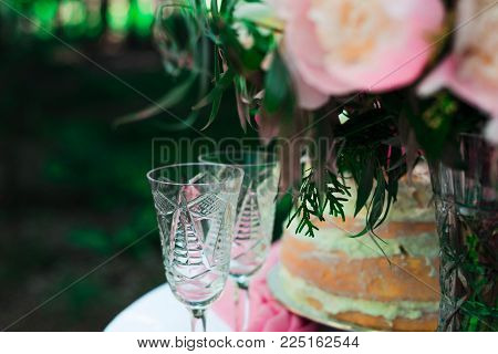 two glasses on the table on the background of flowers and cake. wedding ceremony in the open air