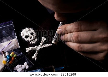 Drug dependence Kills. Junkie man sniffing a line of cocaine in the shape of a skull through a dollar, sachets with a dose, pills. Black background. Narcotics concept.