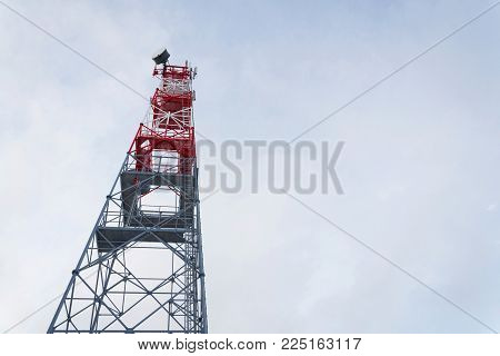 Transmitters and aerials on telecommunication tower, sunset in snowy country