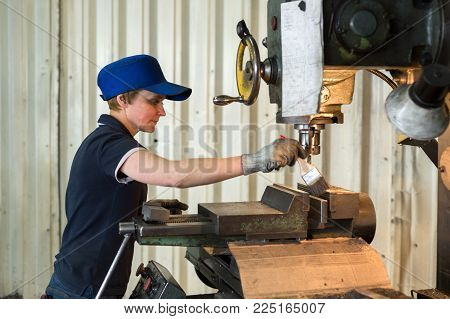 LIPETSK, RUSSIA - JUNE 15, 2017: Lipetsk Machine Tool Plant, A woman at work on a vertical milling machine. Machining of a metal part on a metal-cutting machine.