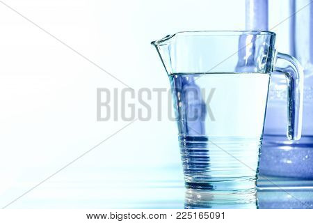 Water diet jug and a bottle on a turquoise background. The picture can also be used to illustrate the problem of protecting clean drinking water.