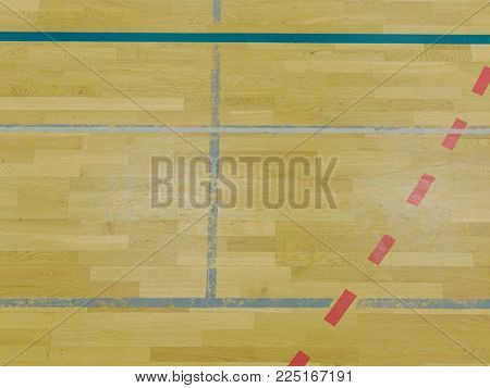 Renewal wooden floor of sports hall with colorful marking lines and new lacquered surface. White black red lines blue playfield in sports hall.