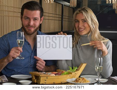 Caucasian young couple at sushi restaurant holding white panel.