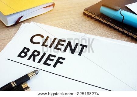 Client Brief On A Wooden Desk With Note.