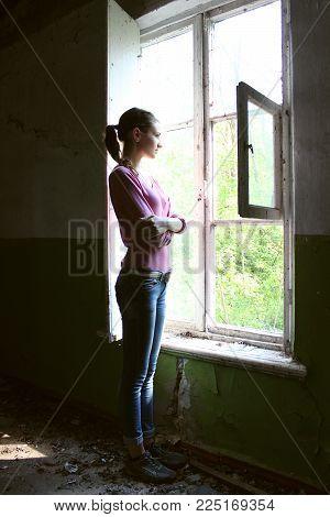 Beautiful girl looking through the old window.