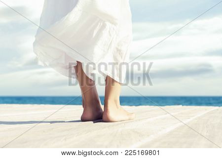 Beautiful feet of a woman in white dress on a wooden pier. Sea and sky background.