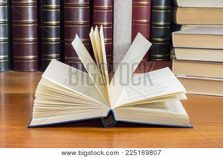 Open book with blue cover on a wooden table at selective focus with blurred text against of the other books on the background