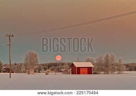 The Super Moon Is Setting Behind The Frosty Forest In The Northern Finland. The Sunrise Colors The S