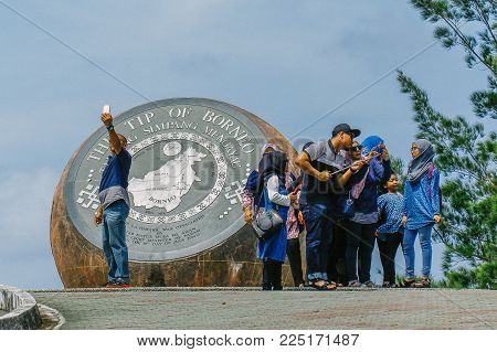 Kudat,Sabah,Malaysia-Feb 3,2018:Group of tourist taking selfie with smartphone with globe monument in the Tip of Borneo in Kudat,Sabah.It is here that the South China Sea lingers & meets the Sulu Seas flowing from the east.