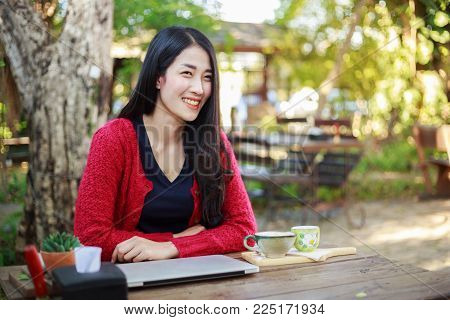 Portrait Of Young Woman With Laptop And Coffee In Garden