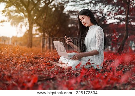 Beautiful Woman Using Laptop And Mobile Phone In The Park