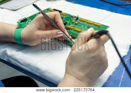The process of assembling an electronic module. The worker's hands place electronic components on the printed circuit board. Workplace assembly plant electronics industry