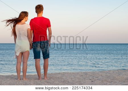 romantic date in the rays of the setting sun, the couple is standing on the beach, the girl and the guy are holding hands, the wind is waving the hair on the beach