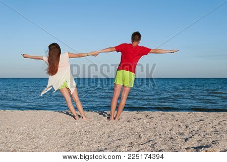 romantic date a girl and a guy hold hands and stretch in different directions, lit by the bright rays of the sun, stand on the sand against the sea