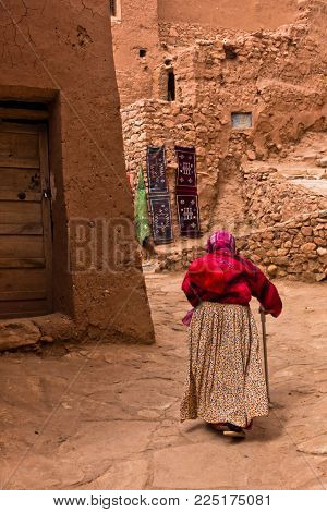 Old Berber Woman At Narrow Street Of Ait Ben Haddou Village, Unesco World Heritage Site In Morocco,