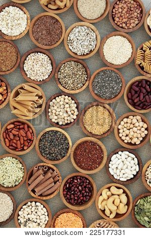 Vegan dried health food with nuts, seeds, legumes, pasta, grains and cereals. Food high in fibre, antioxidants, anthocyanins, vitamins and minerals. Top view on hessian background.