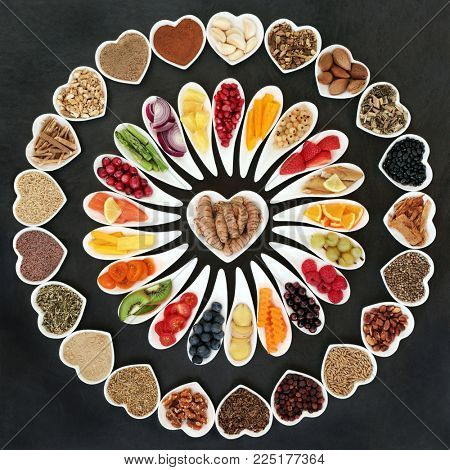 Health food for a healthy heart with vegetables, fruit, fish, nuts, seeds, supplement powders, pulses, cereals, spices and herbs used in herbal medicine. High in omega 3, anthocyanins, & antioxidants