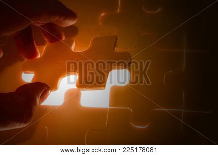 Hand holding a missing jigsaw puzzle piece with light glow, business concept for completing the final puzzle piece