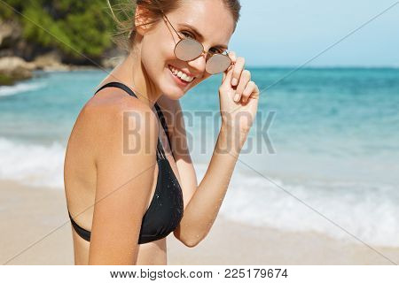 Cropped View Of Beautiful Female In Sunglasses And Swimwear, Happy To Spend Summer Vacations Abroad