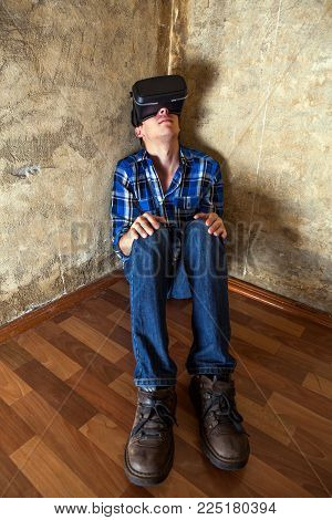 Young Man in Virtual Reality Glasses sit on the Floor by the Old Wall