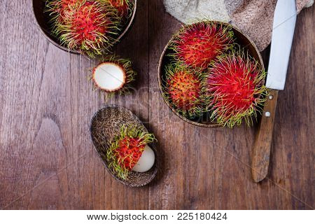 Fresh Rambutans In A Woodean Bowl On Wooden Background.