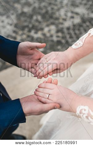 Newly married loving couple holding hands with rings.