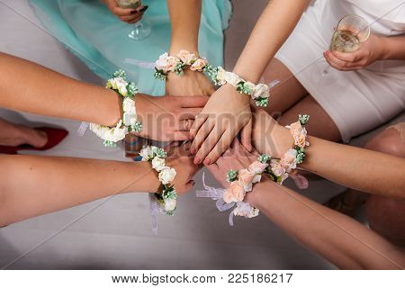 The girlfriends of the bride and the bride are sitting in a circle and holding hands. Hands are decorated with flower bracelets. Cropped image