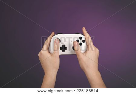 Female Hands Holding Gamepad isolated agains a color background