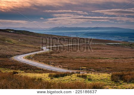 Hartside Pass near sunset, in the North Peninnes, Cumbria with Eden Valley and the snow capped mountains of the Lake District beyond