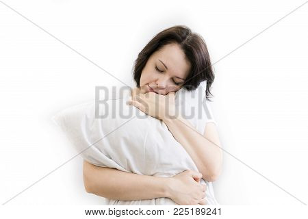 Young woman sitting on bed, hugging pillow, smiling