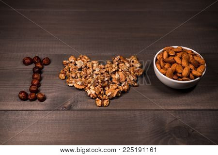 Inscription I love nuts, from nuts, walnuts, almonds and hazelnuts and one white cups with nuts. On brown wooden background.