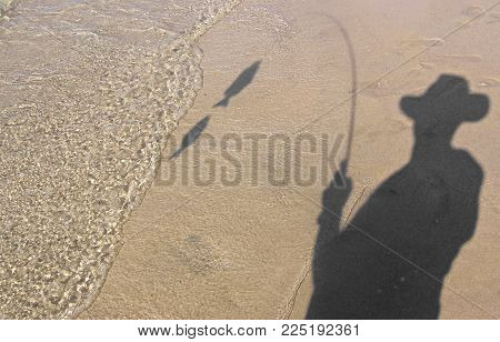 Shadows of a man fishing and his catch on the beach sands.