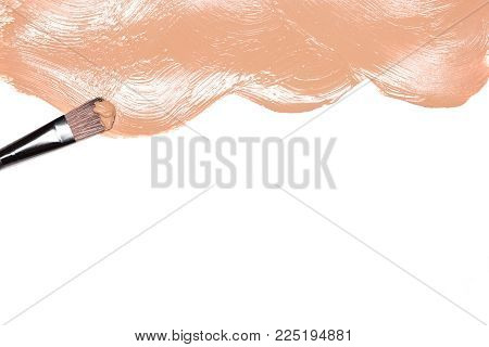 Flat makeup brush with smeared liquid foundation on white with space for text. Make-up background